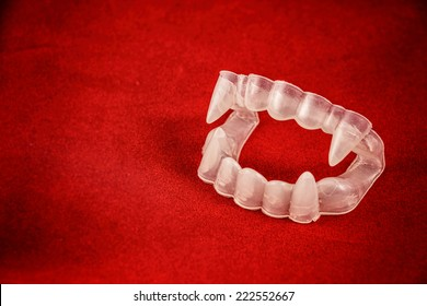 Vampire Costume Fangs on Red. Classic Halloween costume vampire teeth with fangs on red.