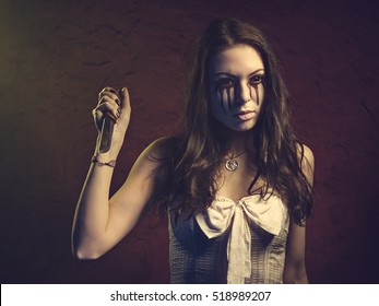 Vampire girl with a knife. Blood leaks from her eyes