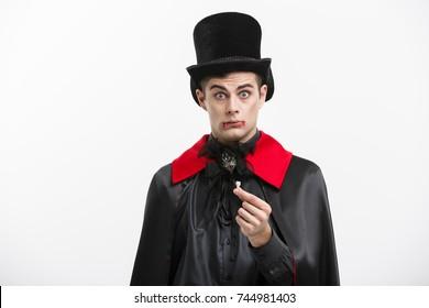 Vampire Halloween Concept - Portrait of handsome caucasian Vampire hurting lose his vampire tooth.