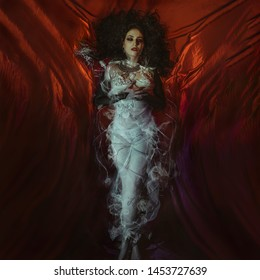 Vampire Halloween Woman portrait. Beauty Sexy Vampire Girl lying in red satin fabric. Vampire makeup Fashion Art design. Attractive model girl in Halloween costume and make up