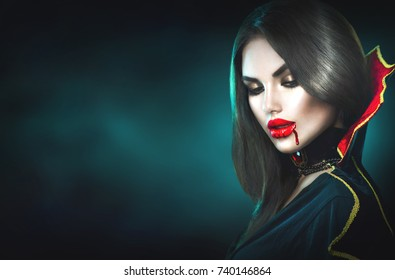 Vampire Halloween Woman portrait. Beauty Sexy Vampire Girl with dripping blood on her mouth. Vampire makeup Fashion Art design. Attractive model girl in Halloween costume and make up. Dark background