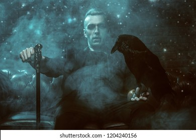 A vampire man with a cane  is sitting on the sofa and holding a black raven. Halloween night. Beauty, fashion.