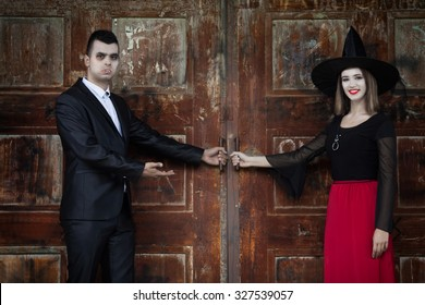 Vampire and witch opening the door of the haunted house and welcoming you to the monster's ball