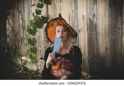 Vampire woman on Halloween night. Witch in magic hat with Pumpkin and knife Halloween Party girl. Smiling woman in witch Halloween costume