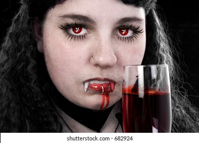 Vampiress with glass of fresh blood.  Reflection of ghostly face in eyes and blood dripping from mouth.