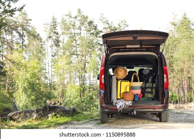 Van with camping equipment in trunk outdoors