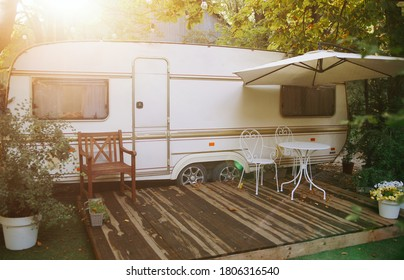 Van mobile home with terrace at sunset in autumn, mobile home, green and orange leaves. noise, film effect