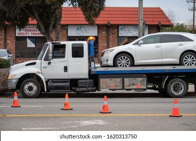 Van Nuys, California / USA  - January 19, 2020: A Tow Industries International brand flatbed tow truck at the scene of a traffic accident investigation in front of 6750 Balboa Blvd.