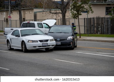 Van Nuys, California / USA  - January 19, 2020: A white Ford Mustang and black Toyota Prius sit in the middle of the road after an accident in front of 6750 Balboa Blvd.