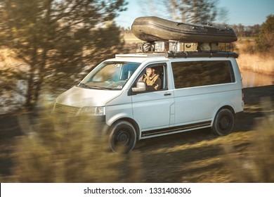 Van with a rubber boat on the roof rack is driving through nature
