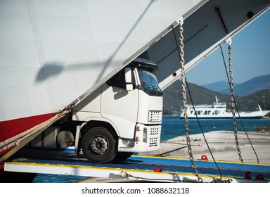 ?argo van, truck, kamion transports goods or items between countries. International transportation concept. Camion rides out of ferry, ferryboat on sunny day. Intercontinental transport.