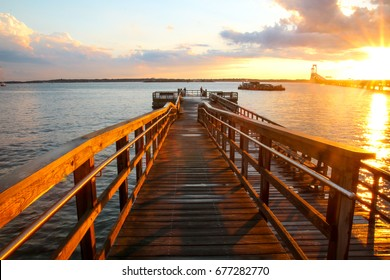 Van Zant Pier after a rainstorm in Newport, Rhode Island. The wooden platform is wet from the rain, during the sunset. In the background is the Newport Bridge and storm clouds. Popular with fishermen