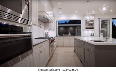 Vancouver - 26. April 2020: Luxurious Dining Room And Modern Kitchen Furnished With Elegant Furniture Inside Of Spacious Interior. Style Design Concept For Dinner Table, Chair, Drawer And Chandelier.