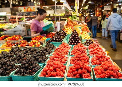 VANCOUVER - AUG 16, 2017: A vendor prepares her fruits for sale at the Granville Island Market. Granville Island is located across False Creek from Downtown Vancouver. Selective focus on fruits.