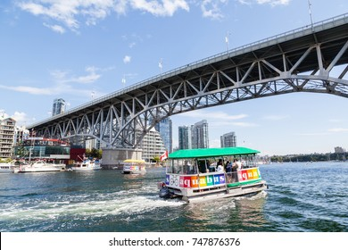 VANCOUVER - AUG. 16, 2017: Visitors to Granville Island taking the Aquabus water taxi across False Creek harbor with the Granville Street Bridge and Vancouver's Yaletown skyline in the background.