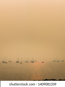 Vancouver, BC - August 22, 2018: Boats moored at English Bay in thick afternoon haze of smoke from inland forest fires.