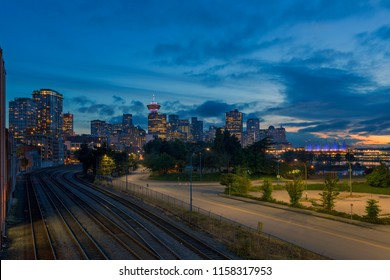 Vancouver BC British Columbia Canada downtown city skyline by railroad tracks during evening blue hour after sunset
