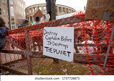 """Vancouver BC, Canada 09/27/2019: a sign that reads """"destroy capitalism before it destroys the planet"""" hanging on a red plastic fence in front of the Vancouver public library"""