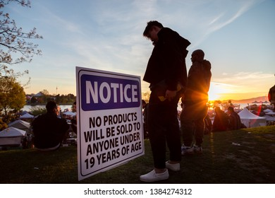 VANCOUVER, BC, CANADA - APR 20, 2019: A young man standing next to a vendor age restriction sign at the 420 festival in Vancouver.