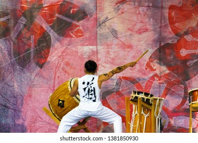 Vancouver, BC / Canada - April 14, 2019: Japanese male artist in white clothes is drumming on traditional Taiko drum at Sakura Days Japan Fair, Vancouver Cherry Blossom Festival.