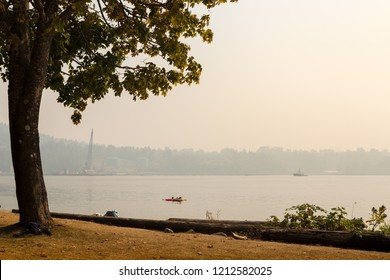 VANCOUVER, BC, CANADA - AUG 20, 2018: Children play in the ocean near a North Vancouver beach with the haze from forest fires obscurring the view.