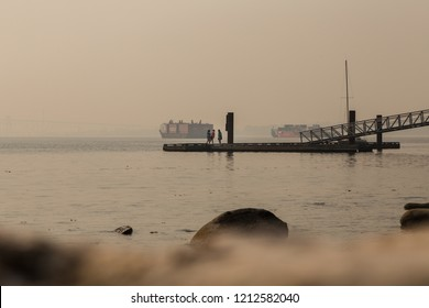 VANCOUVER, BC, CANADA - AUG 20, 2018: Children play on a dock near the ocean near a North Vancouver beach with the haze from forest fires obscurring the view.