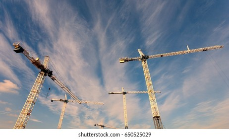Vancouver BC, Canada: Construction cranes against blue sky with cirrus clouds.