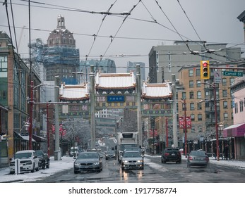 Vancouver, BC CANADA - February 13, 2021. Historic Chinatown Millennium Gate in downtown Vancouver on a winter day with snow falling.