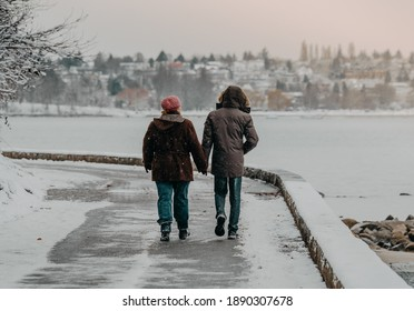 Vancouver BC Canada. January 2020. couple holding hands walking on sea wall with winter snow backgrounds