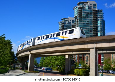 VANCOUVER BC CANADA JUNE 13 2015: The Skytrain elevated light rapid transit system crossing over a busy street, Vancouver, BC, Canada
