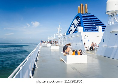 Vancouver, BC, Canada - June 29, 2017: Passengers on Deck of a BC Ferries Vessel in Navigation between Victoria and Vancouver. BC Ferries provides a link from mainland British Columbia to the islands.