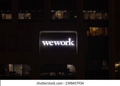 Vancouver, BC \ Canada - March 12 2019: A night shot of a logo of WeWork company on a side of a building.