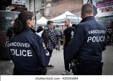 VANCOUVER, BC, CANADA - MAY 11, 2016: Vancouver Police Officers on patrol in front of a flea market in Vancouver's Downtown Eastside.