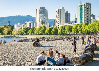 Vancouver, BC / Canada - May 2018: An evening walk along Sunset Beach and English Bay in downtown Vancouver, where hundreds of people gather to hang out and enjoy nature.