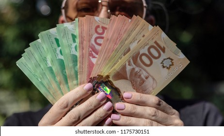 Vancouver, BC / Canada - September 8th 2018 : A Woman Fanning Out Canadian Cash