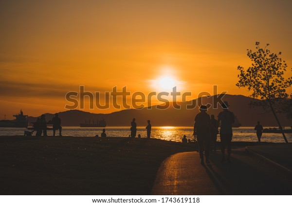 Vancouver BC Canada,April 2020.people on sea wall enjoying sunset during the Covid_19