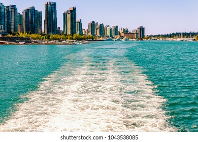 Vancouver BC,Canada A foam path in the ocean from a ship near the shore near a modern city with tall buildings, forest and yachts on the grass plan on a summer day