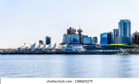 Vancouver. BC/Canada-May 24, 2019:  View of the Vancouver Downtown Skyline and Harbor with the sails of the Cruise Terminal building on the left. Viewed from the Stanley Park Seawall pathway