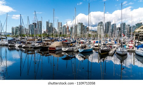 Vancouver, British Columbia - Canada. 04 August 2017. Boats and buildings mirroring in the English Bay waters.