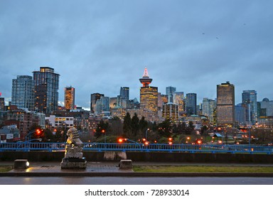Vancouver, British Columbia, Canada, 2012. Skyline of the city from a wet street closed to the harbor at dusk lit by many artificial lights