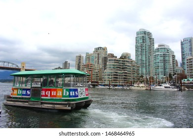 Vancouver, British Columbia / Canada - April 15 2017: Aquabus ferry leaving Granville island on False Creek, with the Vancouver skyline in the background