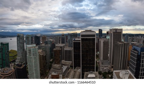 Vancouver, British Columbia, Canada - July 1, 2018: Aerial panoramic view of the modern Downtown City Skyline during a cloudy sunset.
