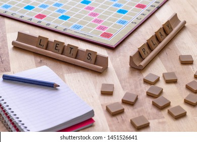 "Vancouver, British Columbia, Canada, - July 13, 2019 - Scrabble board game with the scrabble tile spell ""Let's Play"""