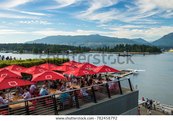 Vancouver, British Columbia / Canada - July 27 2017: People dining on one of the many restaurant patios that line Coal Harbour in Vancouver, Canada.