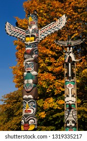 Vancouver, British Columbia, Canada - October 28, 2008: Kakasolas and Chief Wakas totem poles in Stanley Park Vancouver with orange maple leaves