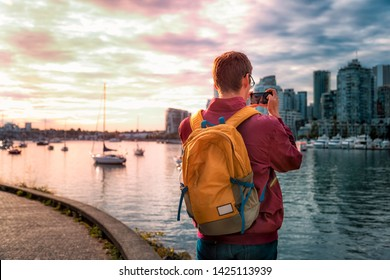 Vancouver, British Columbia / Canada - September 24th 2018: Tourist taking photo of False Creek at sunset, Vancouver, British Columbia, Canada, North America