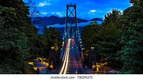 Vancouver, British Columbia. Canada View from above of the Lions Gate Bridge with lights trail, glitters and clouds.