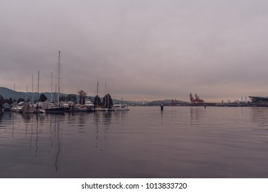Vancouver, British Columbia/Canada - December 24 2017: waterfront in downtown with boats reflecting in the water at dusk.