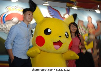 VANCOUVER, CANADA - AUGUST 10, 2013: A couple pose with Pikachu character mascot during local Pokemon video games tournament in Vancouver, Canada, August 10, 2013.