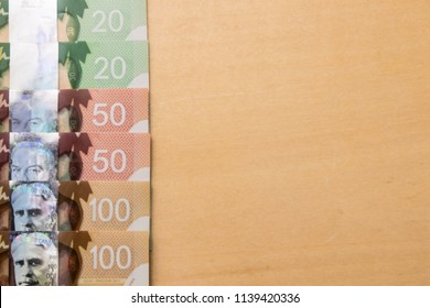 Vancouver, Canada – August, 2017: Close up of Canadian dollar banknotes on wood table background. Business and Finance concepts